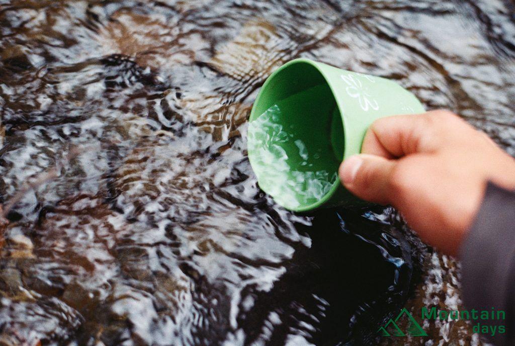 川で水をすくうコップ