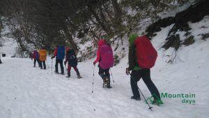 寒い中レインウェアやハードシェルを着て歩く登山者たちの写真